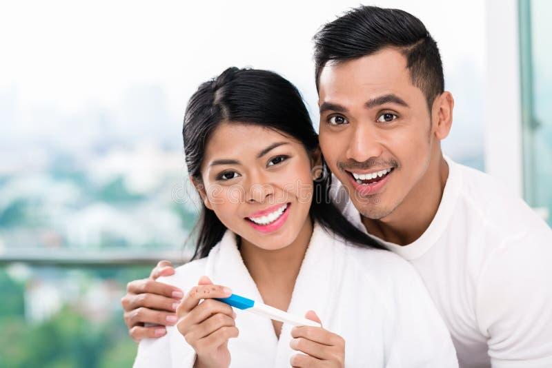 Coppie asiatiche con il test di gravidanza a letto fotografie stock