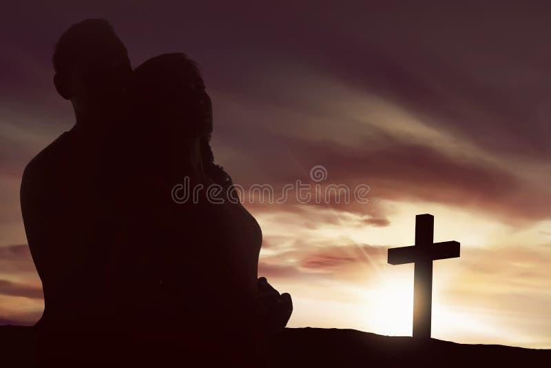 Coppie asiatiche della siluetta che sembrano forma trasversale cristiana fotografia stock