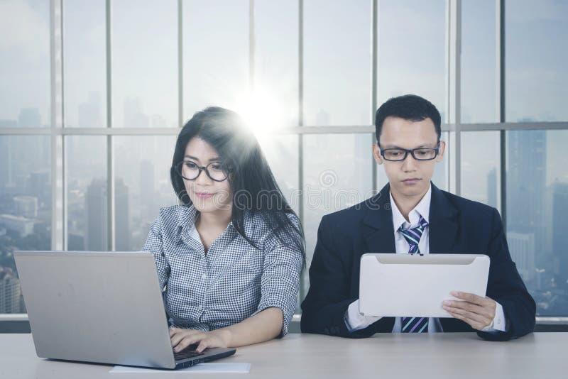 Coppie asiatiche di affari che lavorano vicino alla finestra immagine stock