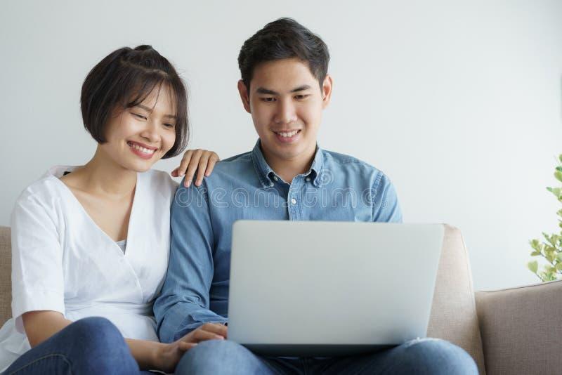 Coppie asiatiche di amore che si siedono sul sofà e che per mezzo del computer portatile essi che sorridono felicemente a casa immagine stock