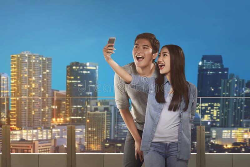 Coppie asiatiche felici che prendono selfie immagini stock