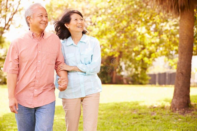 Coppie asiatiche senior che camminano insieme attraverso il parco immagini stock libere da diritti