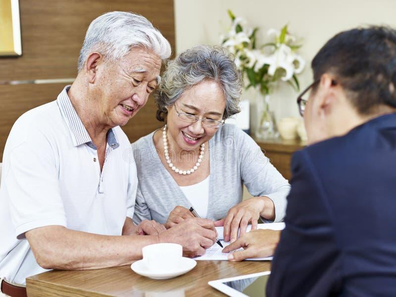 Coppie asiatiche senior che firmano un contratto fotografie stock
