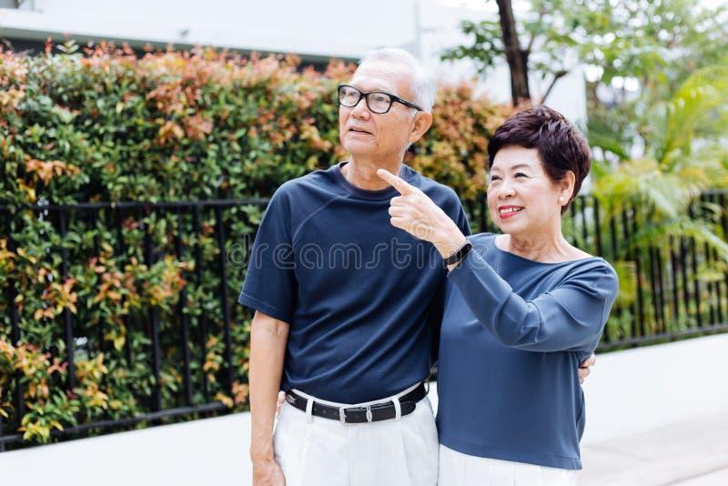 Coppie asiatiche senior felici che camminano e che indicano nel parco e nella casa all'aperto fotografia stock libera da diritti