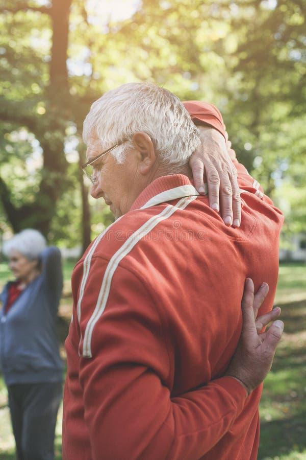 Coppie attive degli anziani che si esercitano nel parco Fuoco su priorità alta fotografia stock libera da diritti