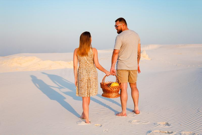 Coppie attraenti adorabili sulla spiaggia di sabbia bianca o nel deserto o nelle dune di sabbia, in tipo ed in una ragazza con un immagini stock