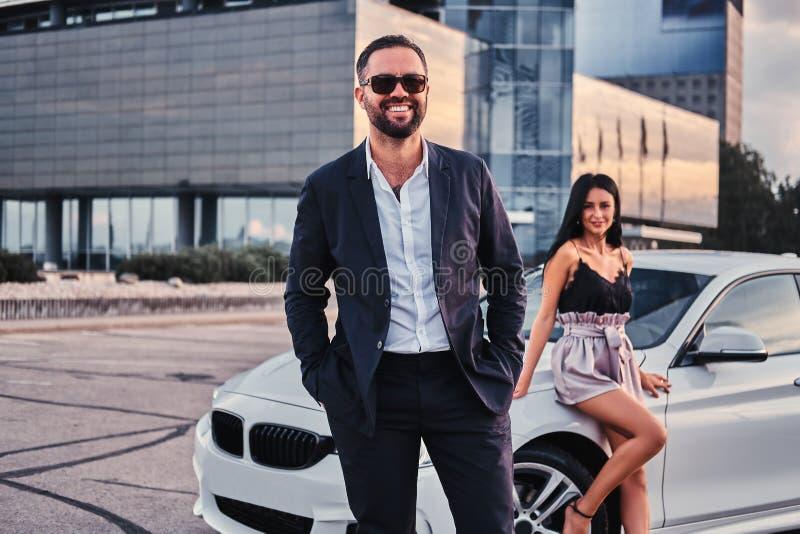 Coppie attraenti ben vestito che si appoggiano un'automobile di lusso all'aperto contro il grattacielo fotografie stock