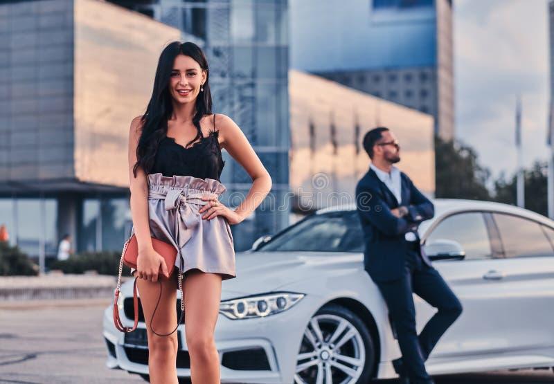 Coppie attraenti ben vestito che si appoggiano un'automobile di lusso all'aperto contro il grattacielo fotografia stock