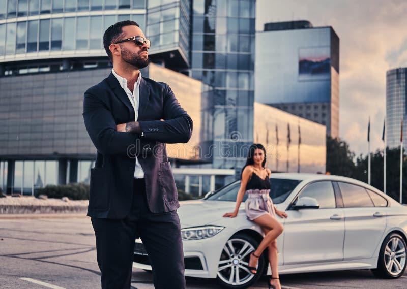 Coppie attraenti ben vestito che si appoggiano un'automobile di lusso all'aperto contro il grattacielo immagine stock