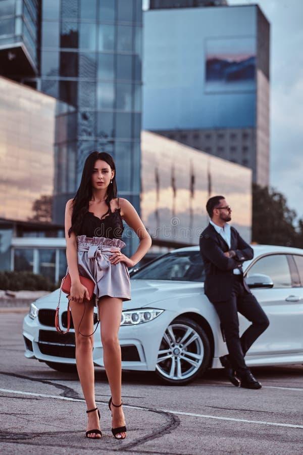 Coppie attraenti ben vestito che si appoggiano un'automobile di lusso all'aperto contro il grattacielo fotografie stock libere da diritti