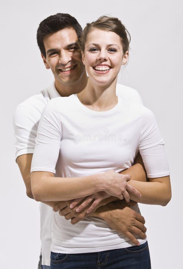 Coppie attraenti che abbracciano e che sorridono immagine stock