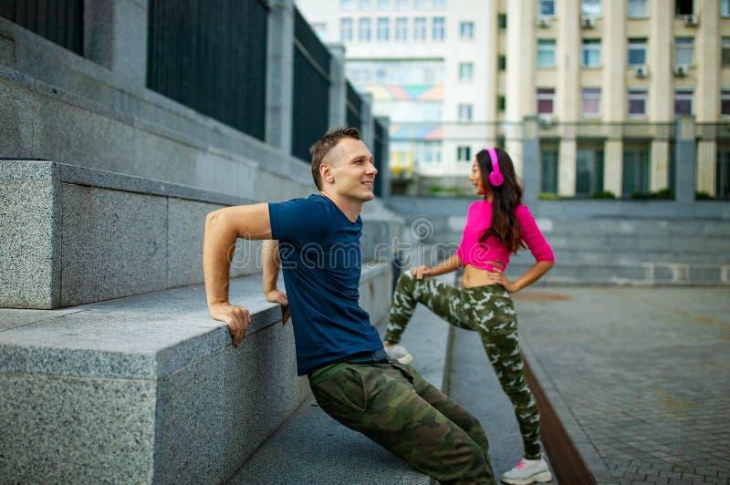 Coppie attraenti che fanno esercizio e che parlano nella città - concetto sano di stile di vita di forma fisica all'aperto fotografie stock