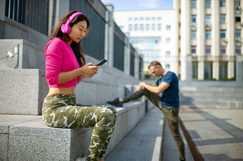 Coppie attraenti che fanno esercizio e che parlano nella città - concetto sano di stile di vita di forma fisica all'aperto fotografie stock libere da diritti