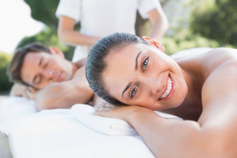 Coppie attraenti che godono del poolside di massaggio delle coppie immagini stock