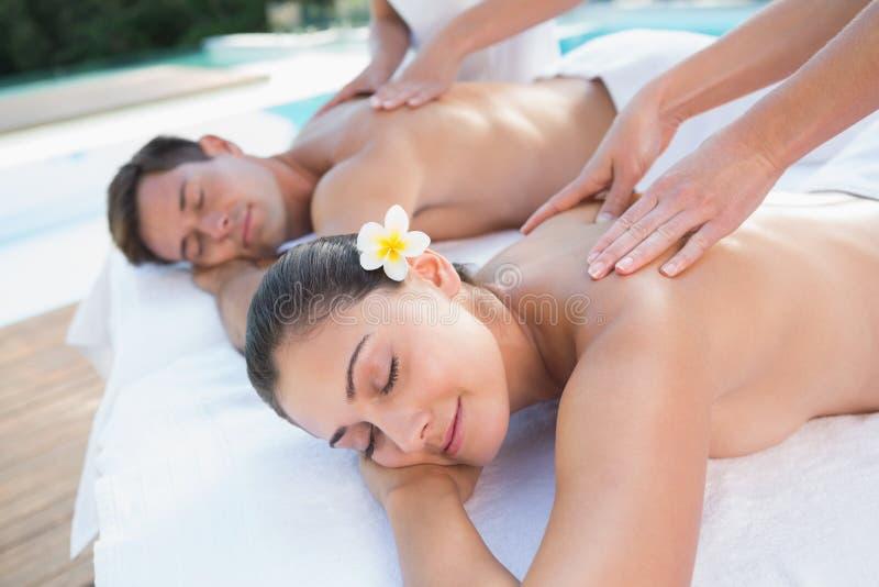 Coppie attraenti che godono del poolside di massaggio delle coppie fotografie stock libere da diritti