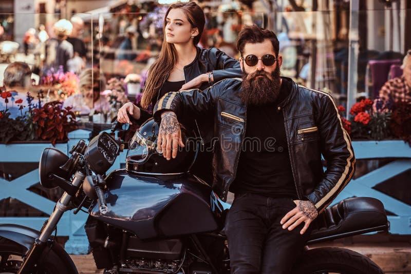 Coppie attraenti dei pantaloni a vita bassa - il maschio brutale barbuto in occhiali da sole si è vestito in un bomber nero e nei fotografia stock libera da diritti