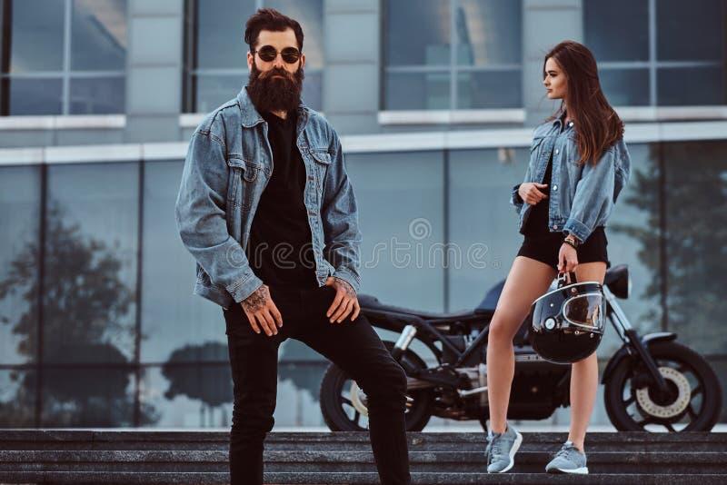 Coppie attraenti dei pantaloni a vita bassa - il maschio brutale barbuto in occhiali da sole si è vestito in un rivestimento dei  fotografia stock