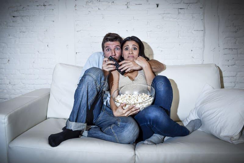 Coppie attraenti divertendosi a casa godere guardando manifestazione di film horror della televisione immagini stock