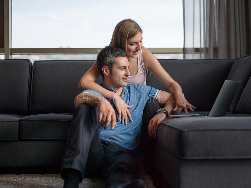 Coppie attraenti facendo uso di un computer portatile sullo strato immagini stock libere da diritti