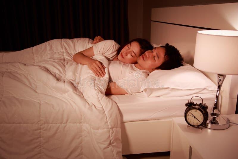 Coppie attraenti felici che abbracciano e che dormono sul letto alla notte fotografia stock libera da diritti