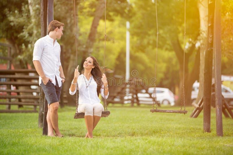 Coppie attraenti in parco su oscillazione fotografia stock