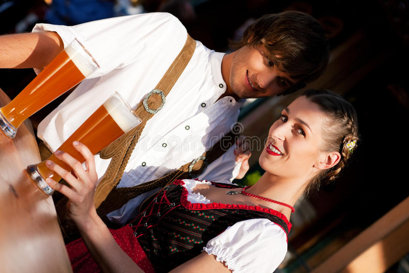 Coppie in birra bevente bavarese del frumento di Tracht fotografia stock libera da diritti
