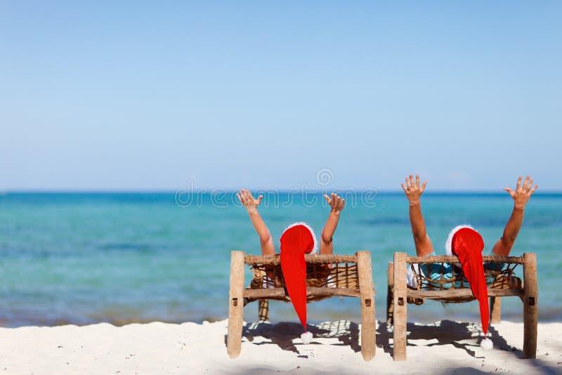 Coppie in cappelli della Santa sulla spiaggia tropicale immagine stock