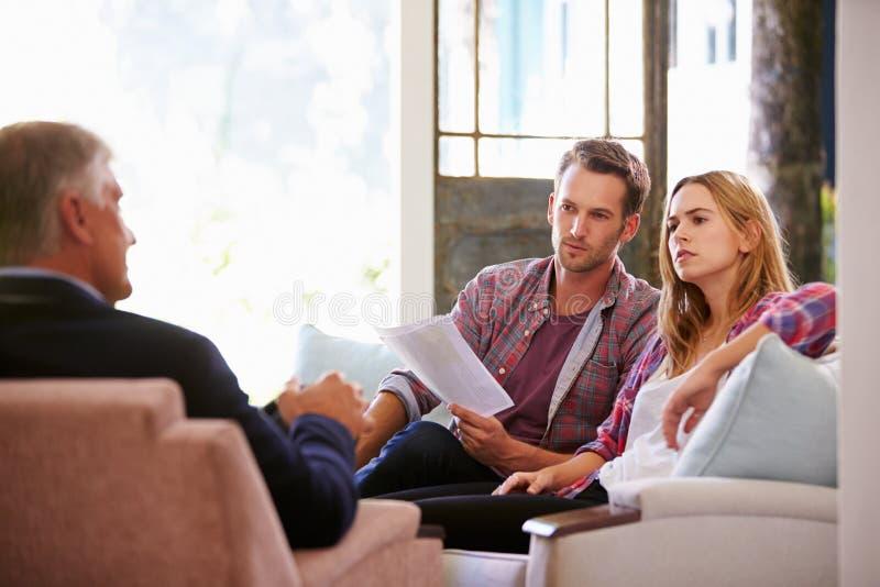 Coppie a casa che incontrano consulente finanziario immagini stock libere da diritti