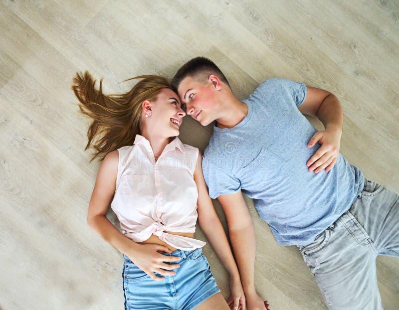 Coppie a casa che si rilassano sul pavimento fotografia stock libera da diritti