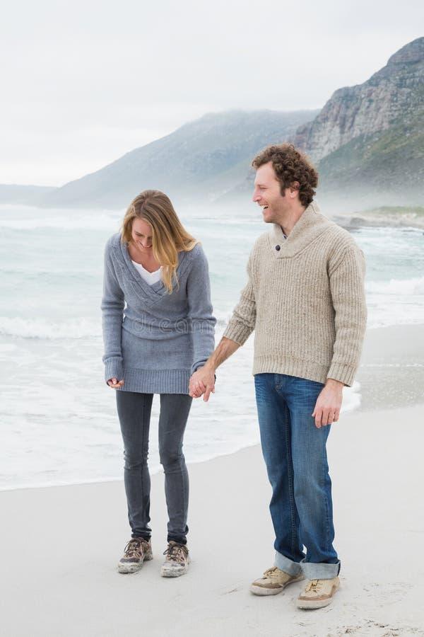 Coppie casuali felici che si tengono per mano alla spiaggia fotografia stock libera da diritti