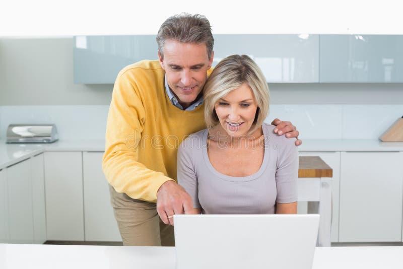 Coppie casuali felici facendo uso del computer portatile in cucina immagini stock
