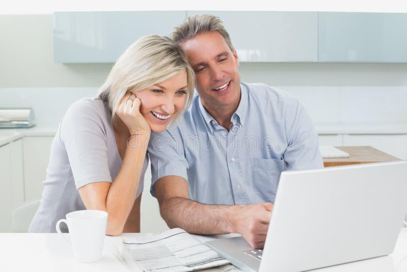 Coppie casuali felici facendo uso del computer portatile in cucina fotografia stock libera da diritti