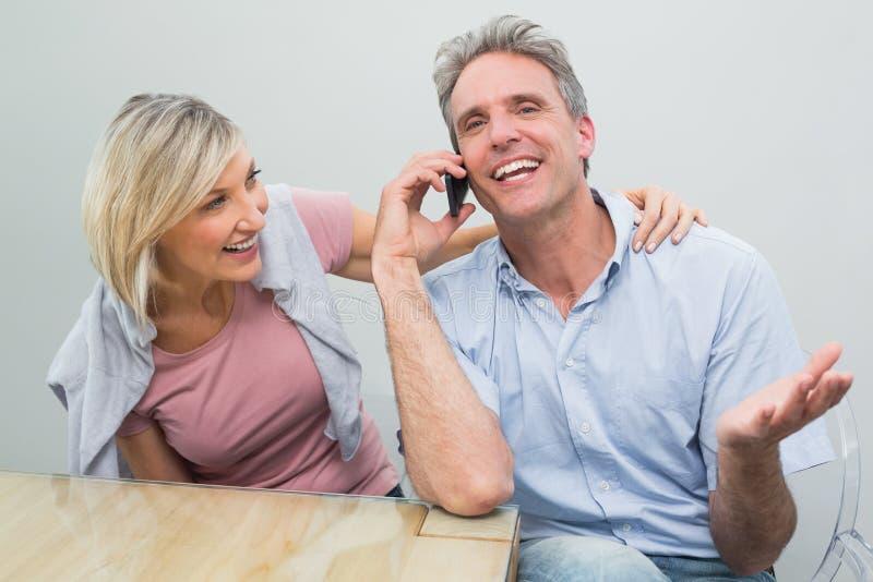 Coppie casuali felici facendo uso del telefono cellulare immagini stock