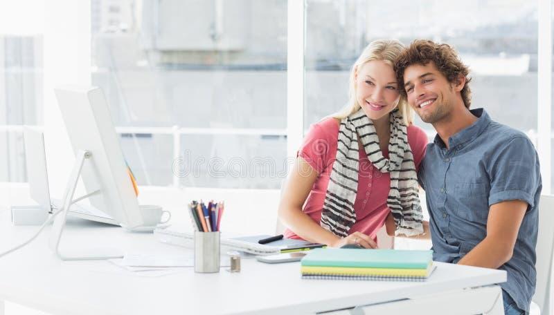 Coppie casuali sorridenti di affari in un ufficio luminoso fotografia stock