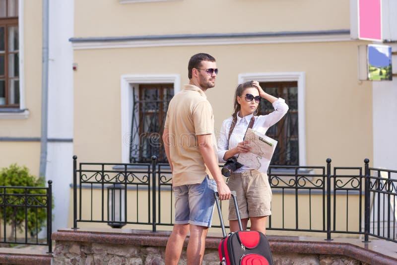 Coppie caucasiche che viaggiano con la valigia del carrello all'aperto Controllo dell'itinerario facendo uso della mappa della ci immagine stock