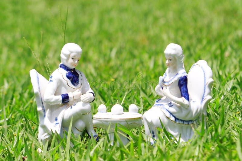 Coppie ceramiche che mangiano tè nel giardino immagini stock libere da diritti