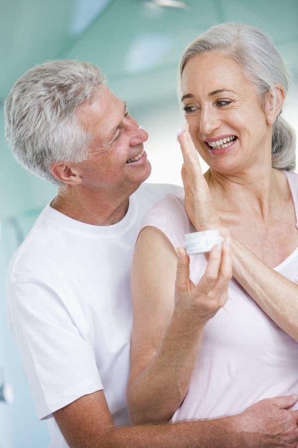 Coppie che abbracciano ad una crema della holding della stazione termale immagini stock