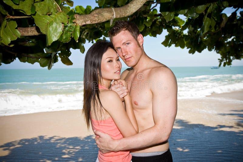 Coppie che abbracciano alla spiaggia fotografia stock libera da diritti