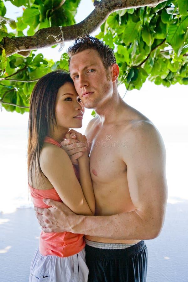 Coppie che abbracciano alla spiaggia fotografie stock
