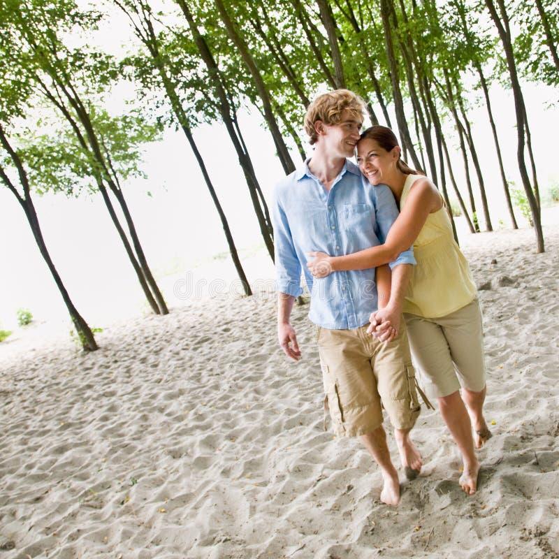 Coppie che abbracciano alla spiaggia immagini stock libere da diritti