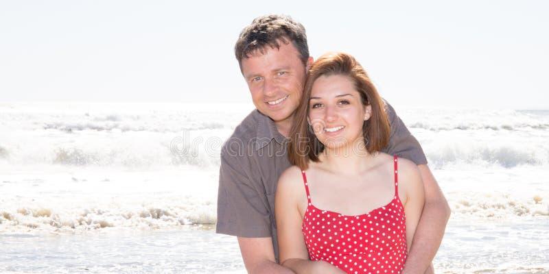 Coppie che abbracciano davanti alla spiaggia dell'oceano del mare fotografia stock libera da diritti