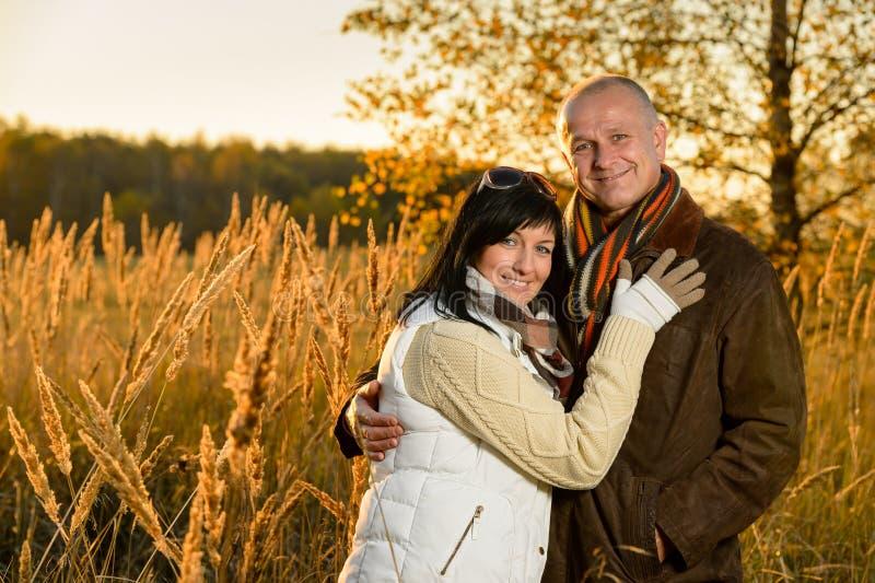 Coppie che abbracciano nel tramonto della campagna di autunno fotografia stock libera da diritti