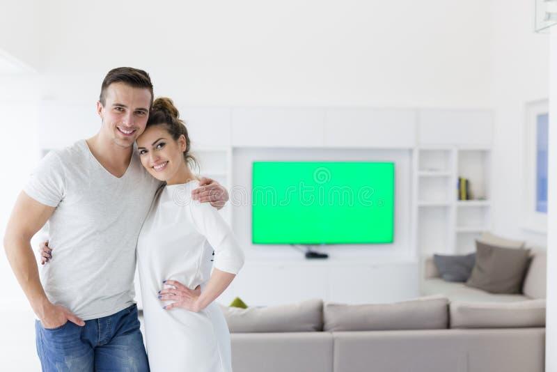 Coppie che abbracciano nella loro nuova casa fotografia stock