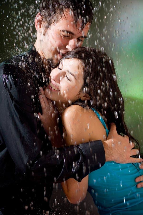Coppie che abbracciano sotto una pioggia immagine stock libera da diritti