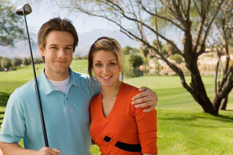 Coppie che abbracciano sul terreno da golf fotografia stock