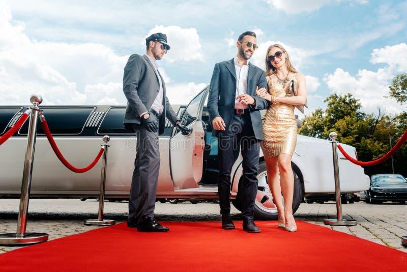 Coppie che arrivano con il tappeto rosso di camminata delle limousine fotografia stock libera da diritti