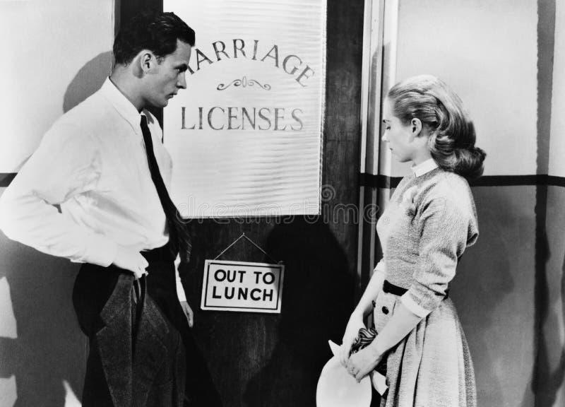 Coppie che aspettano fuori dell'ufficio della licenza di matrimonio (tutte le persone rappresentate non sono vivente più lungo e  immagine stock