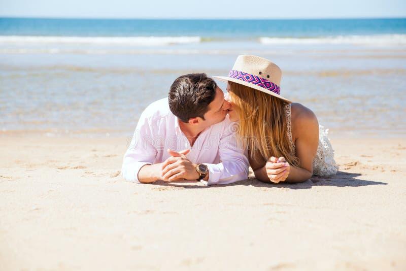 Coppie che baciano alla spiaggia immagini stock