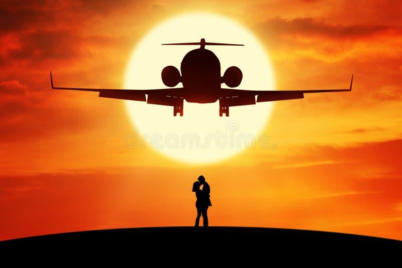 Coppie che baciano sotto l'aeroplano di volo fotografia stock libera da diritti