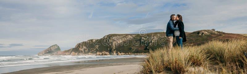 Coppie che baciano sulla spiaggia fotografia stock